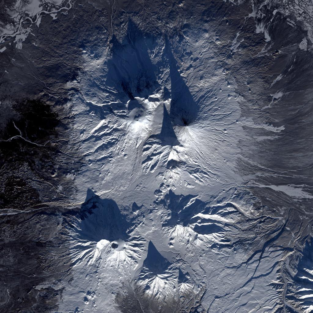 En este detalle de la imagen podemos ver hasta siete volcanes proyectando su alargada sombra sobre la nieve y la gélida superficie de la península de Kamchatka. Landsat/NASA/USGS.