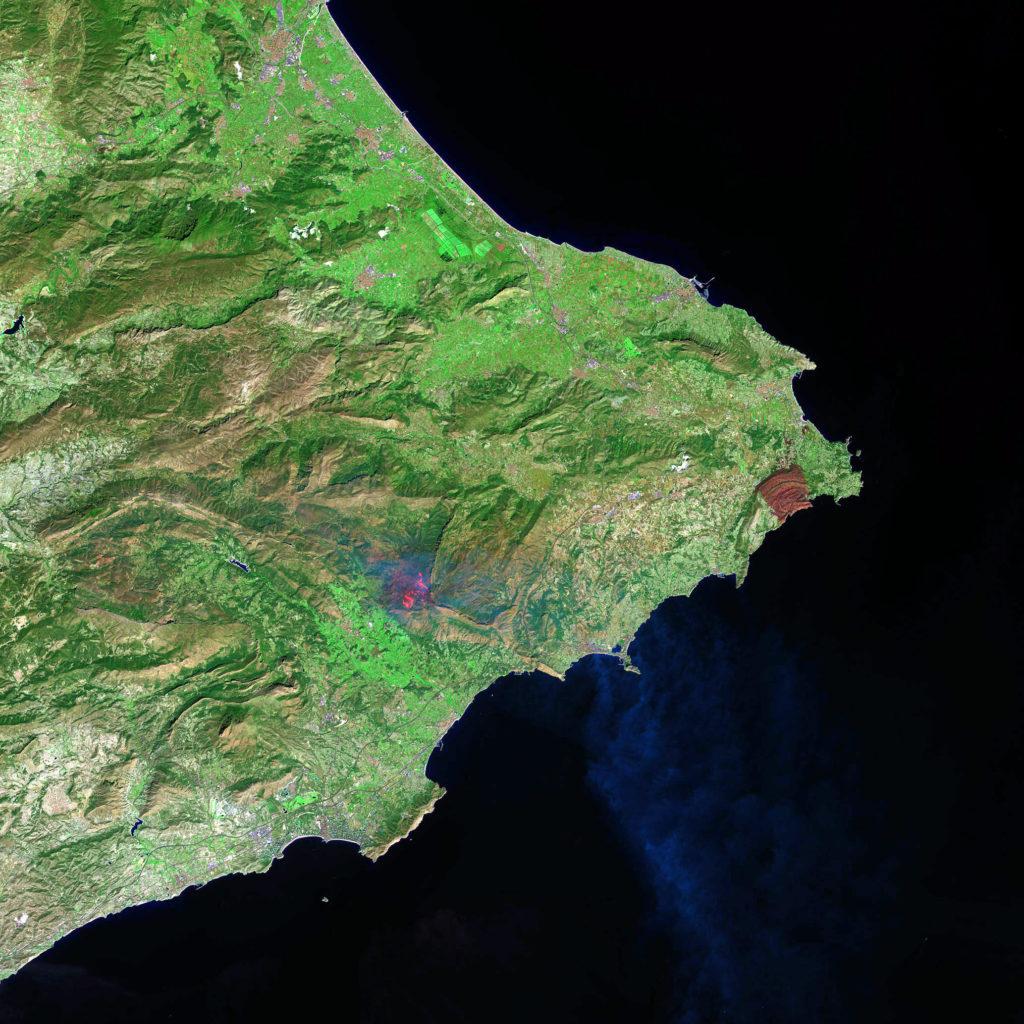 Imagen de falso color en la que podemos apreciar perfectamente la superficie de vegetación quemada, en color marrón oscuro. Además, en el incendio de Bolulla se aprecian perfectamente las llamas, en un color naranja intenso, gracias a las bandas infrarrojas del Landsat 8. NASA/USGS.