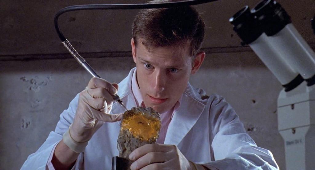 Un científico extrae atentamente sangre de un mosquito encerrado el el interior del ámbar en Parque Jurásico.