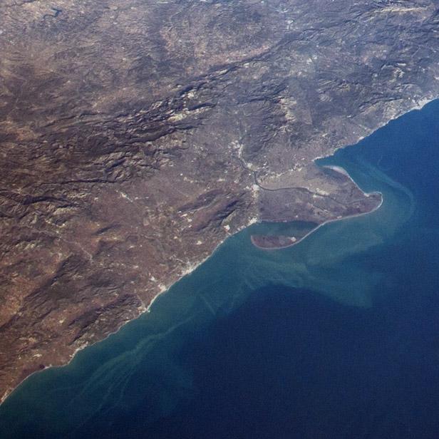 Un detalle de la imagen en la que se observa el delta del Ebro y los sedimentos costeros moviéndose sobre el azul más profundo del Mediterráneo. NASA.