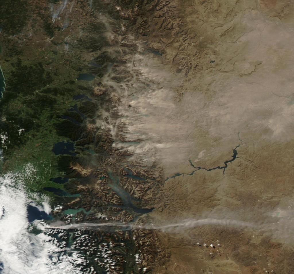 Abajo a la izquierda, el volcán Calbuco se puede ver emitiendo una pequeña columna de cenizas, y arriba se puede ver como el viento mueve la ceniza ya depositada sobre las montañas cercanas el día 25 de Abril. NASA.