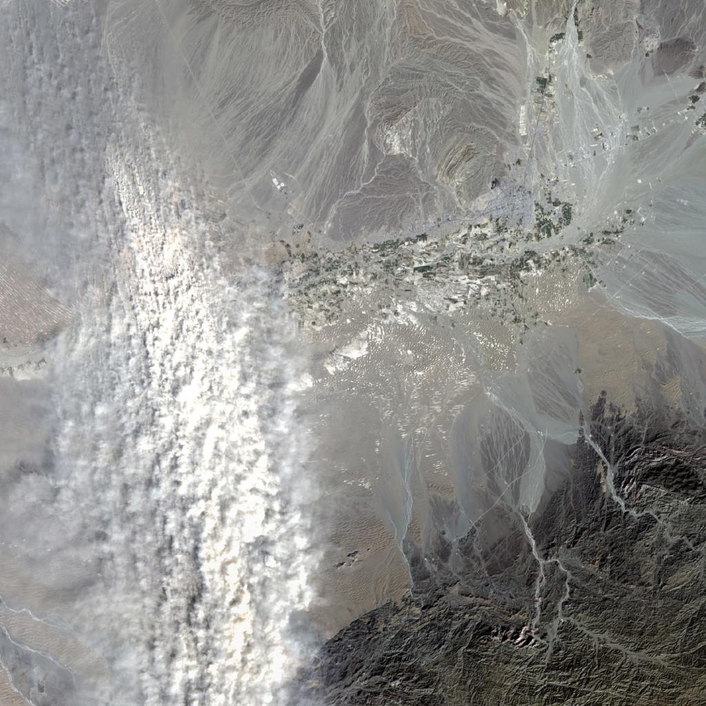 La ciudad de Iranshahr es visible en la mitad derecha de la imagen, y a la izquierda, parte de una tormenta de polvo. Landsat/NASA/USGS