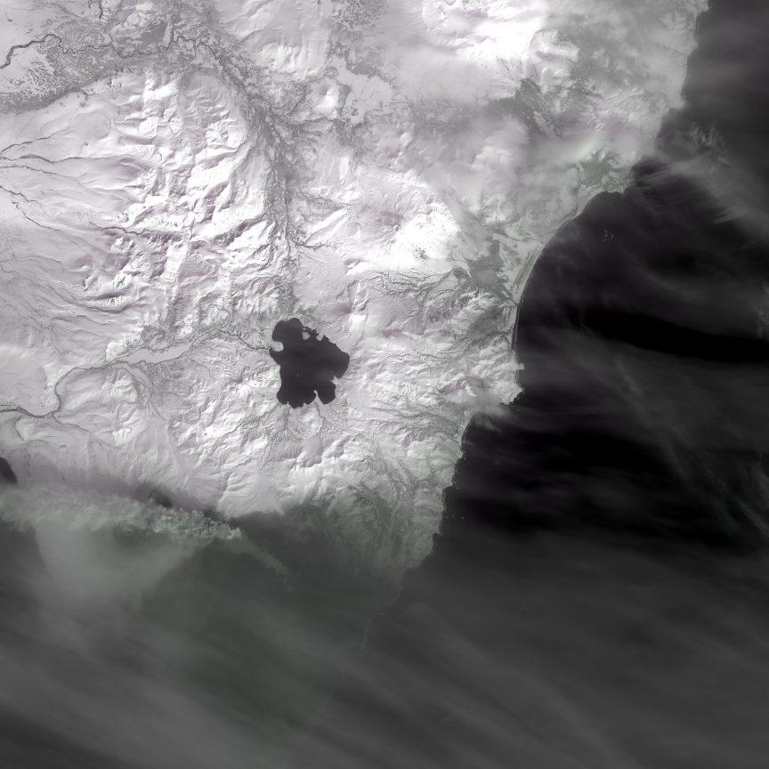 El Kambalny, en la parte inferior izquierda de la imagen, destaca por su columna de cenizas en esta imagen del Landsat 8. NASA/USGS.
